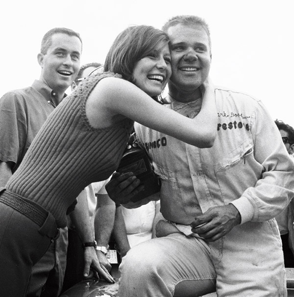Mark Donohue is congratulated for his victory in the 1966 Nassau Trophy race as Roger Penske looks on.