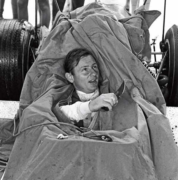 A well-armed Bruce McLaren emerges from a tarpaulin covering the M7 Formula One car during a rainy testing session at Brands Hatch in 1968.
