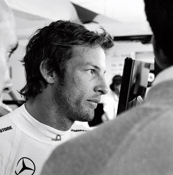 Flanked by engineers in the McLaren garage, Jenson Button stares at a monitor showing his results from a practice session at the British Grand Prix at Silverstone in 2010.